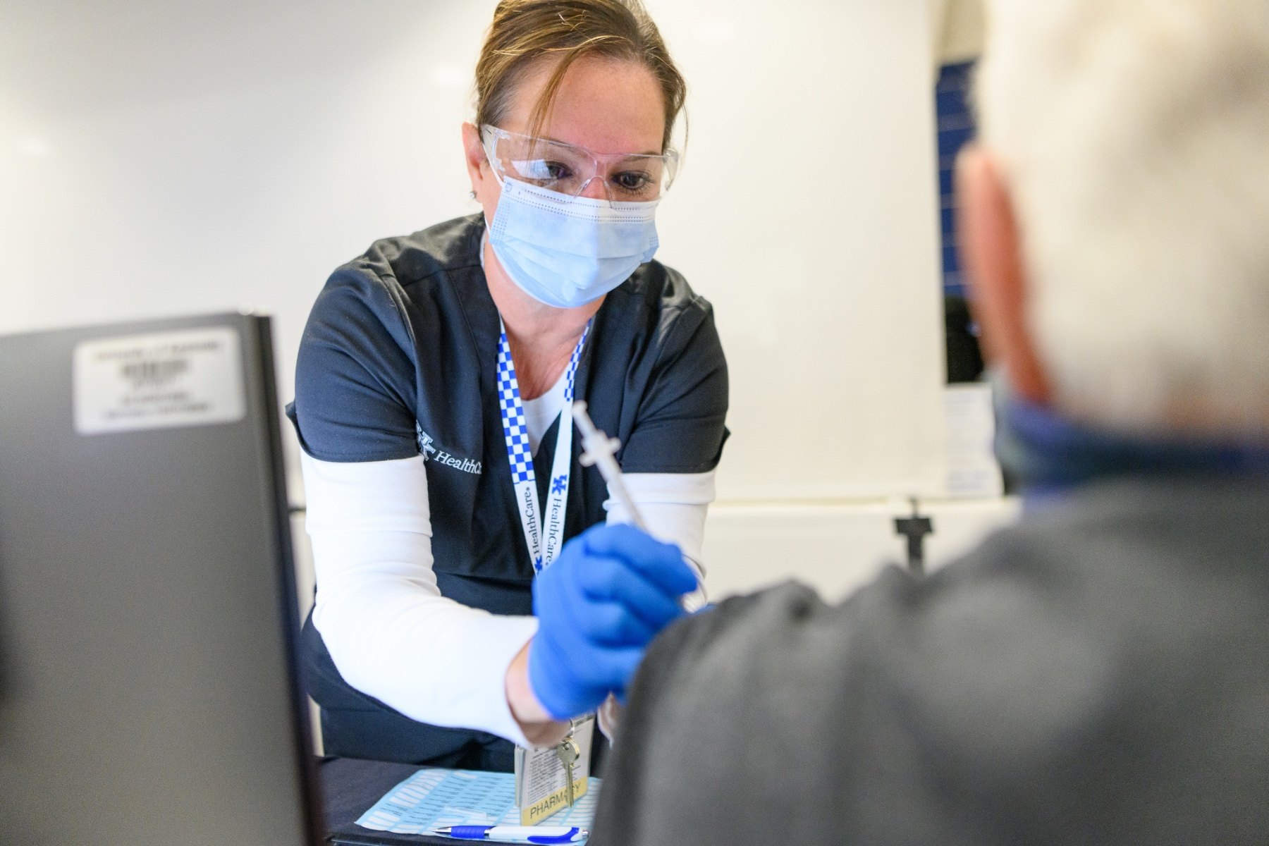 A female UK HealthCare staff member is administering the COVID vaccine to an older gentleman.