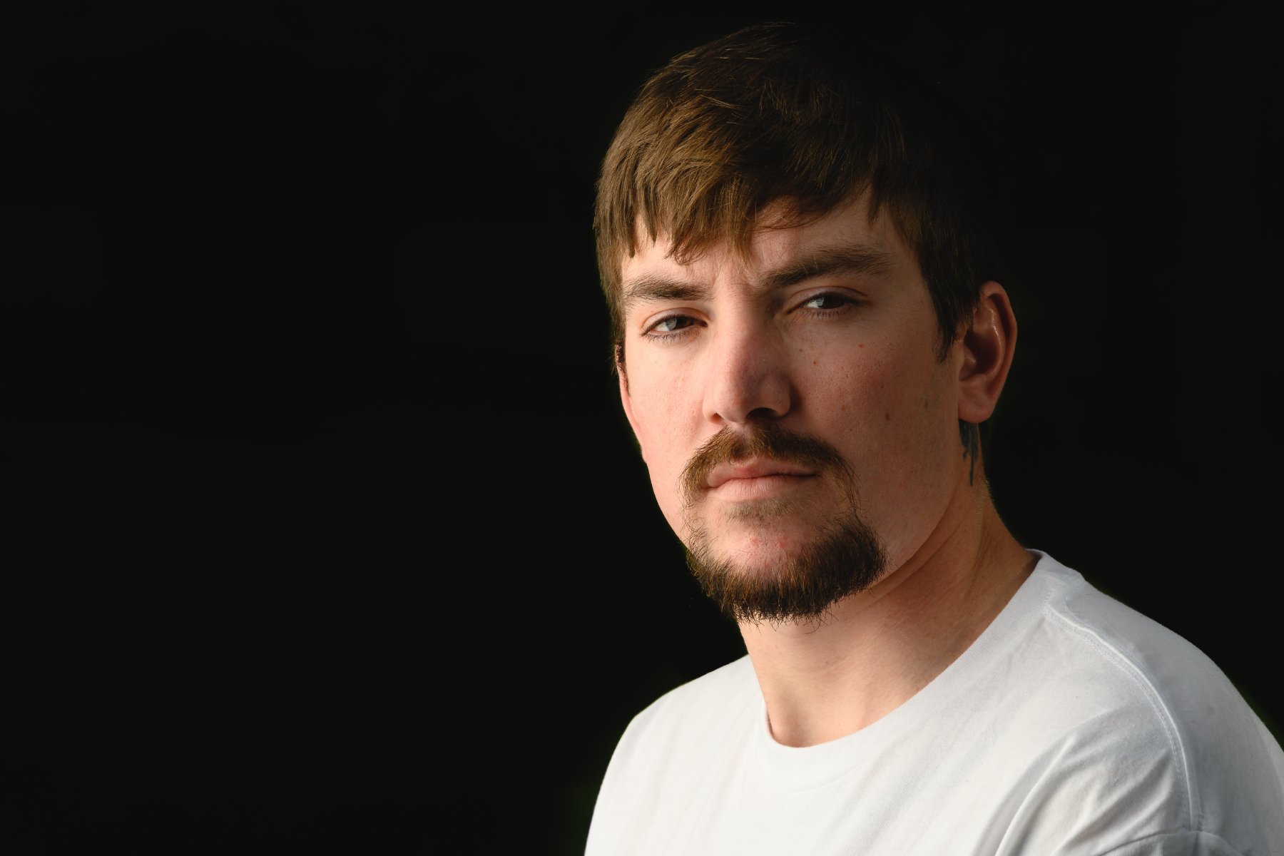 Cameron Waters, a white adult male with brown hair, wearing a white shirt stares straight into the camera with a black background.