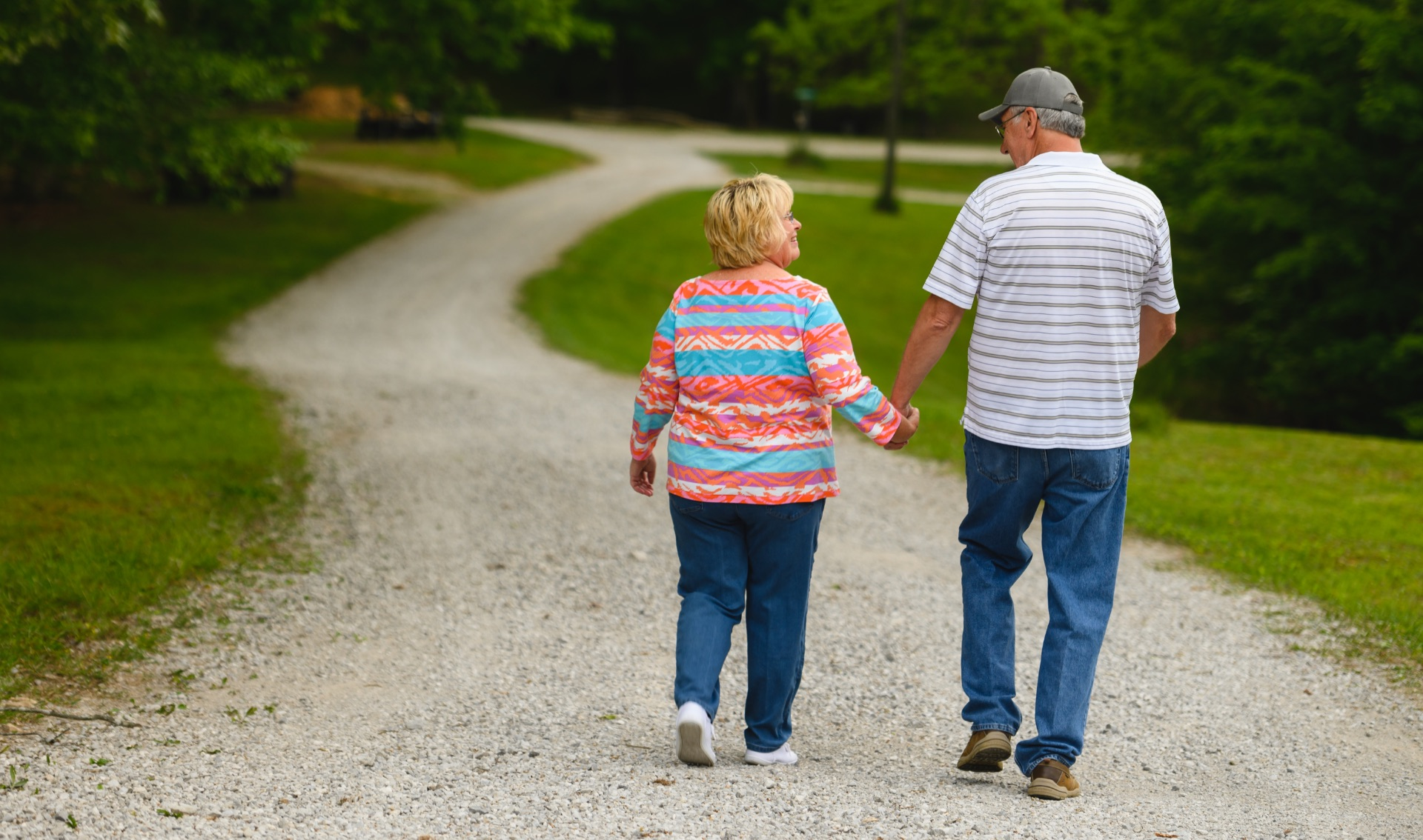 Danny and his wife, an older white woman with blonde hair, walk down a path at a park.
