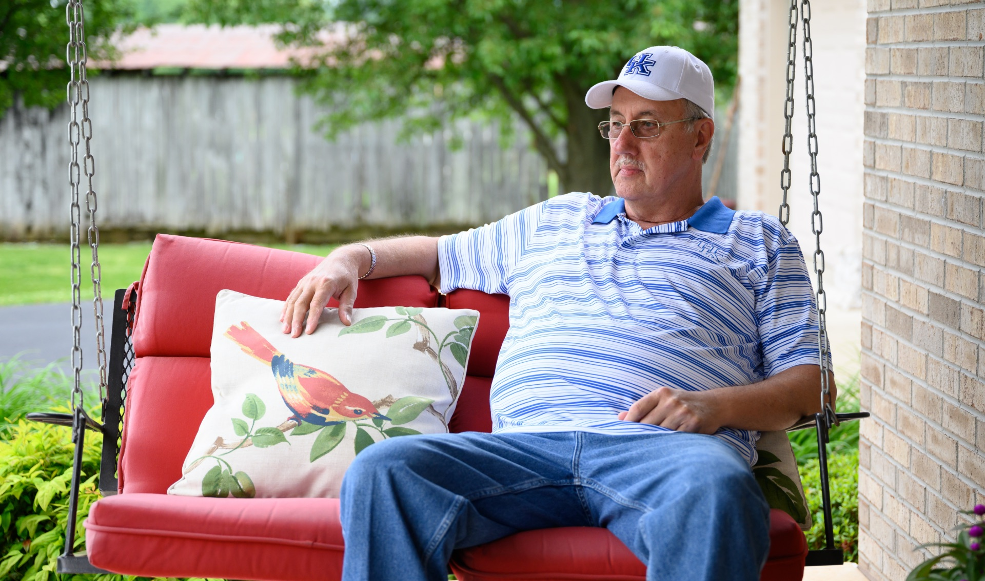 Danny sits out on the porch in a blue and white striped shirt with a white and blue UK cap.