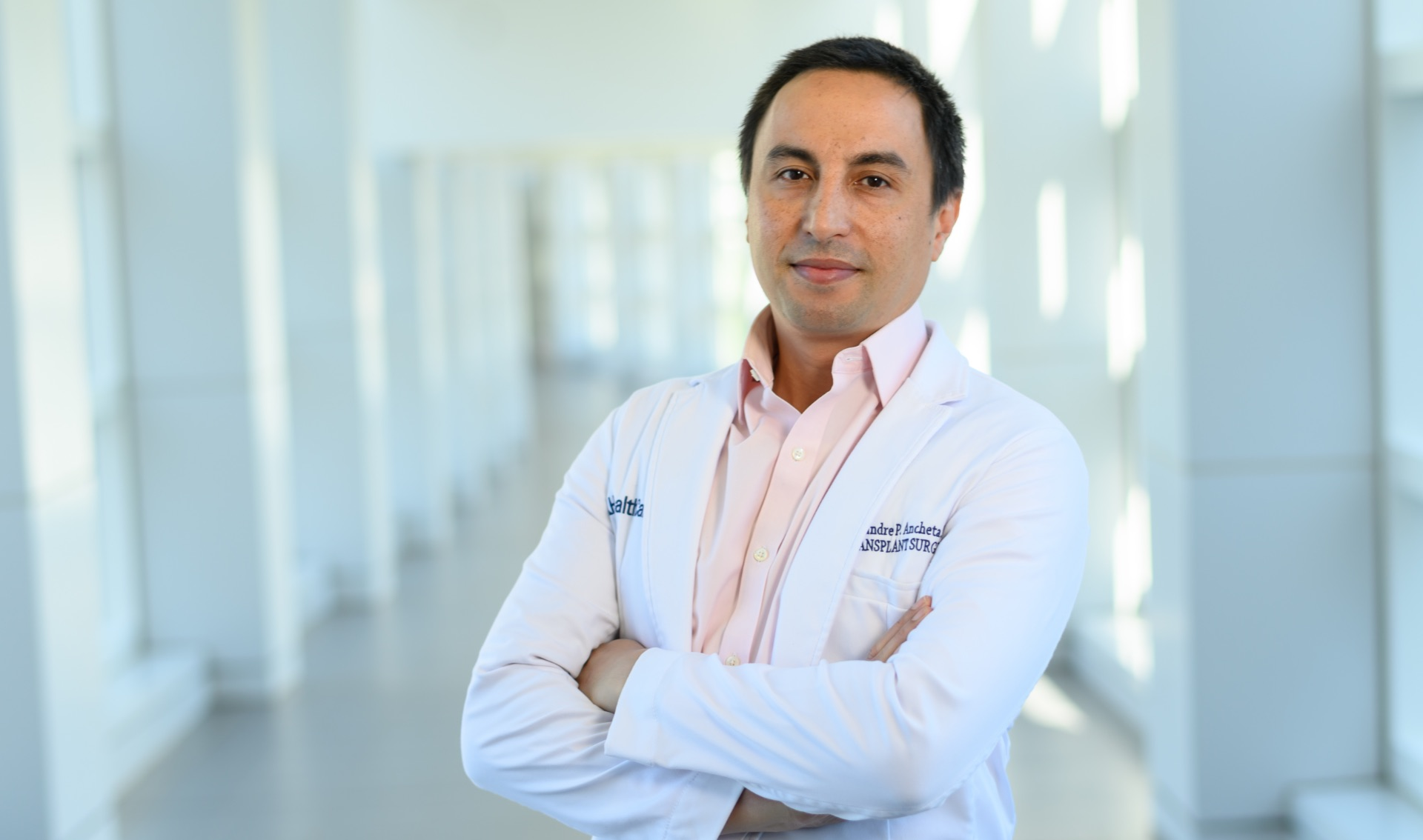Dr. Alexandre Ancheta, a middle aged man with short black hair, stands in the hallway of UK HealthCare, wearing a white doctor's coat and a pink shirt.