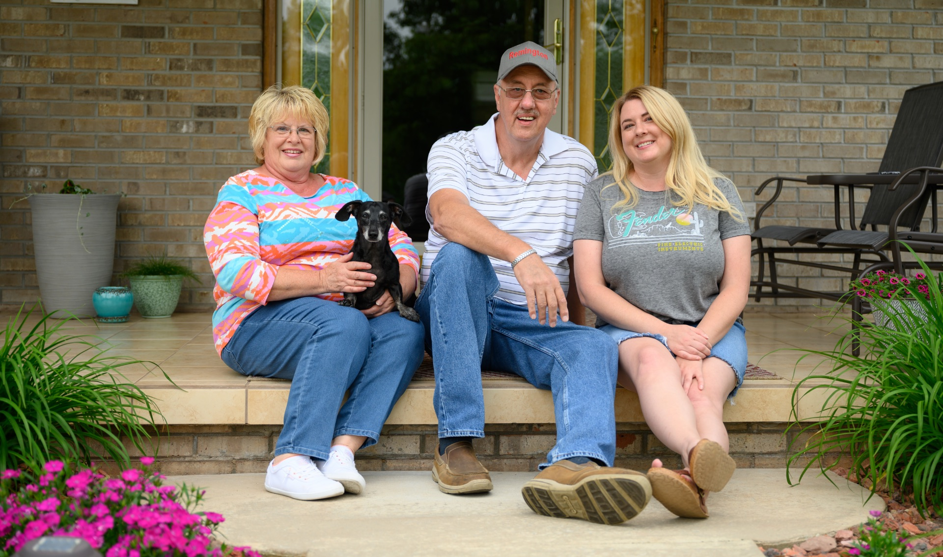 Danny, his wife, and his daughter—a middle-aged woman with blonde hair—smile and sit side by side in front of the house.