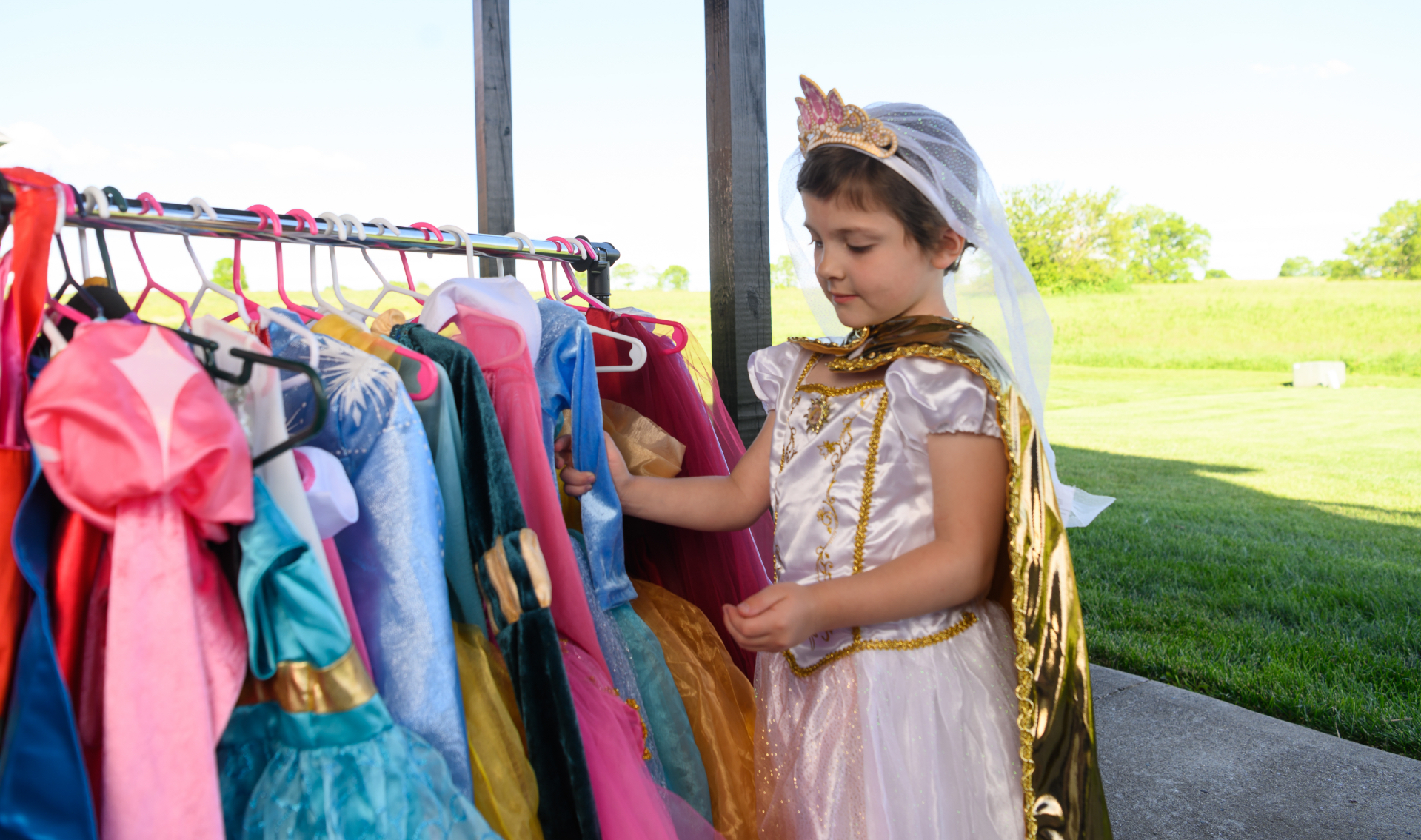 Leorah admires a rack of her costumes while wearing one herself.
