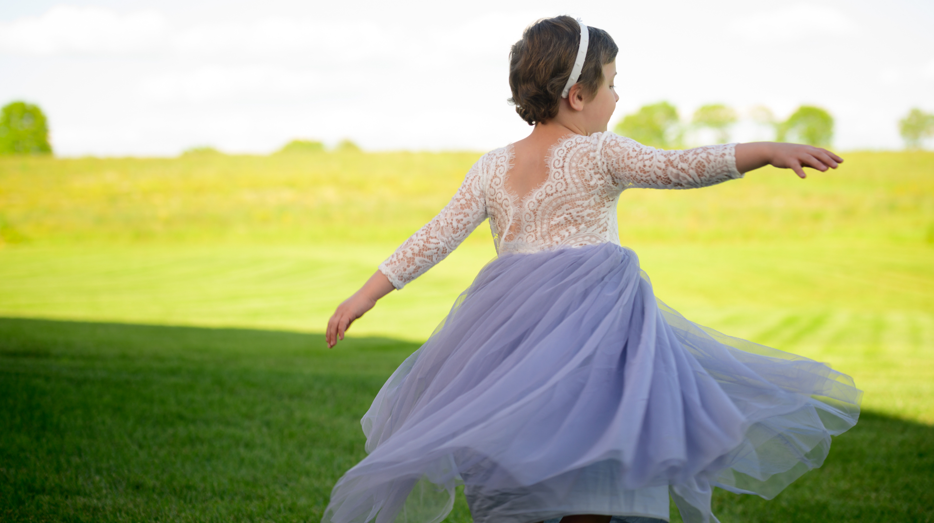 A photo of Leorah from behind as she twirls in an open field, her arms extended.