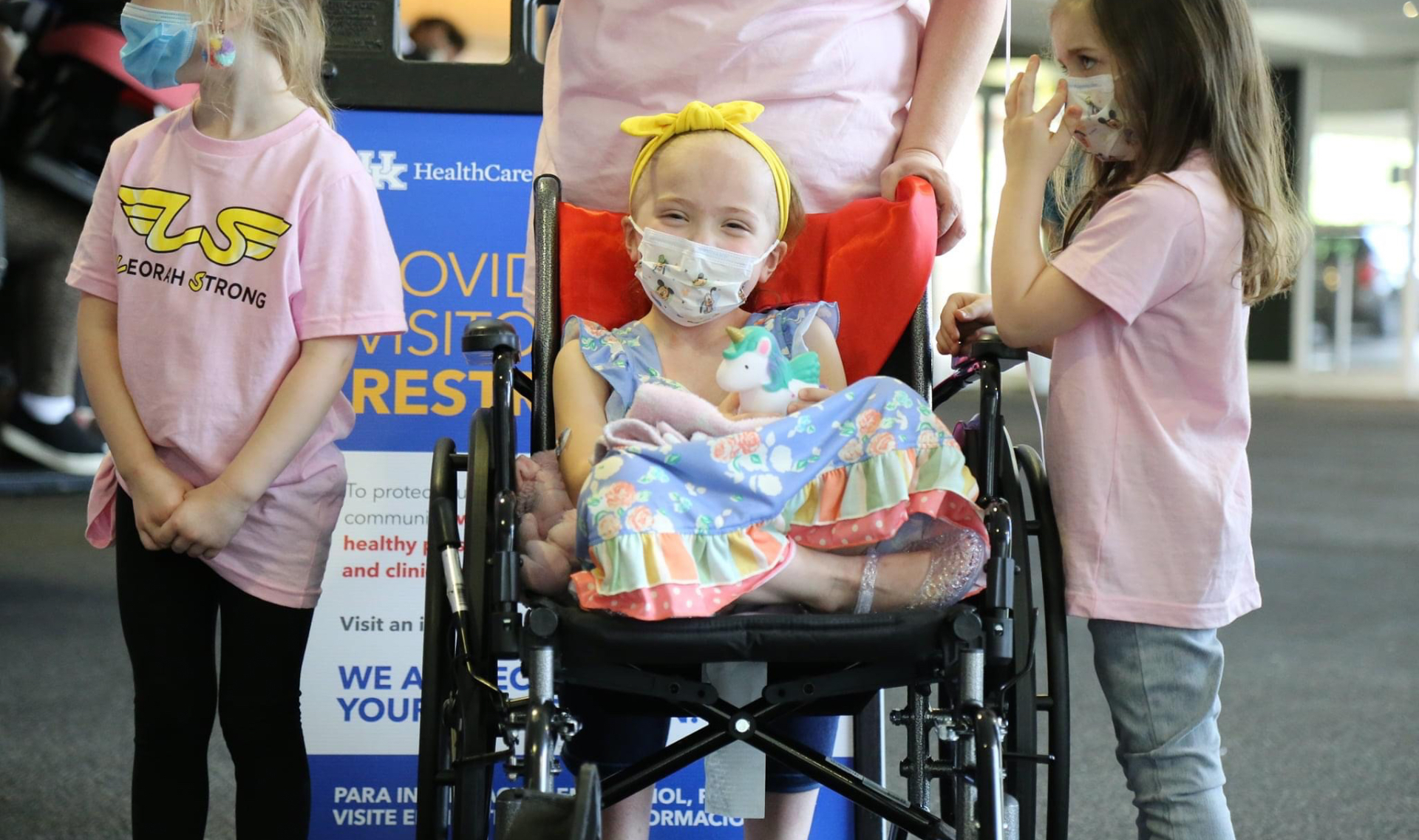 """Leorah sits in her wheelchair, legs crossed and visibly smiling from behind her medical mask, with two young girls by her side. Both of these young girls are white, wearing pink """"Lenorah Strong"""" t-shirts and jeans and both have medium-length hair, one blonde and one brunette."""