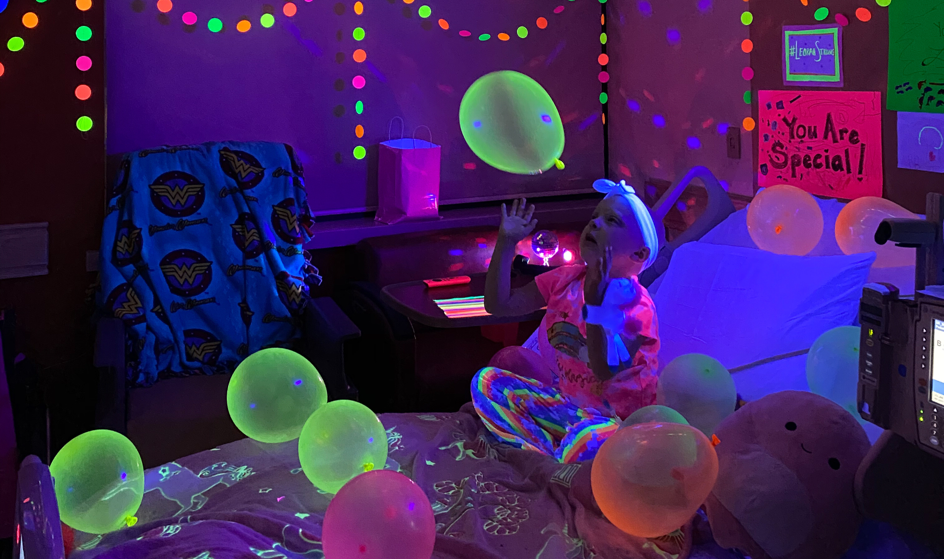 Lenorah plays with a balloon while sitting on her hospital bed, which is being illuminated by a blacklight. The room is filled with balloons and streamers, all of which are glowing.