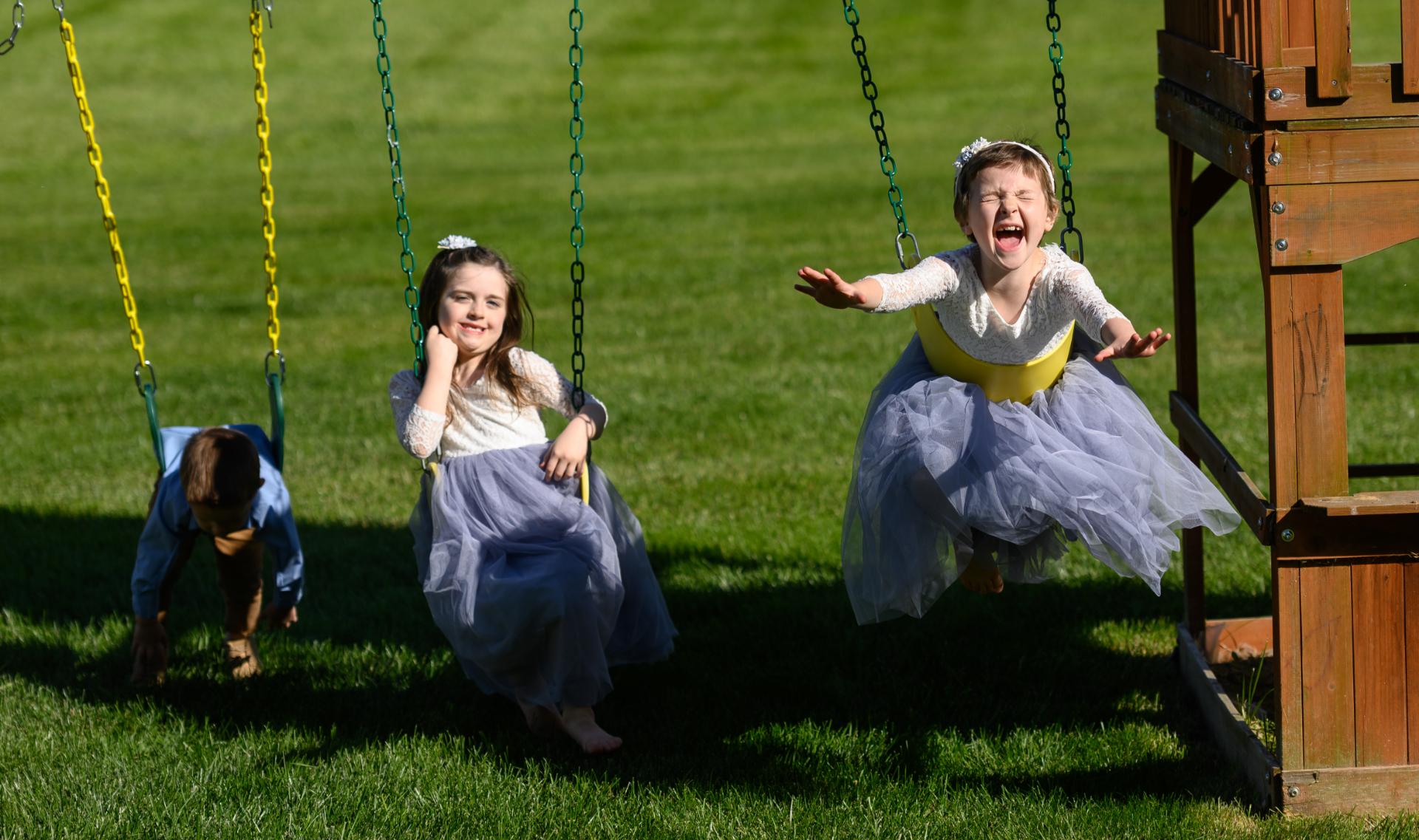 Leorah and her siblings play on their swingset, with Lenorah and her younger brother swinging while laying on their stomachs. Her brother is a young white boy, younger than his sisters, and is wearing a blue button-up and brown slacks. Her sister is a young white girl with brown hair, and is wearing a dress made of lace at the top and light blue tulle at the bottom.