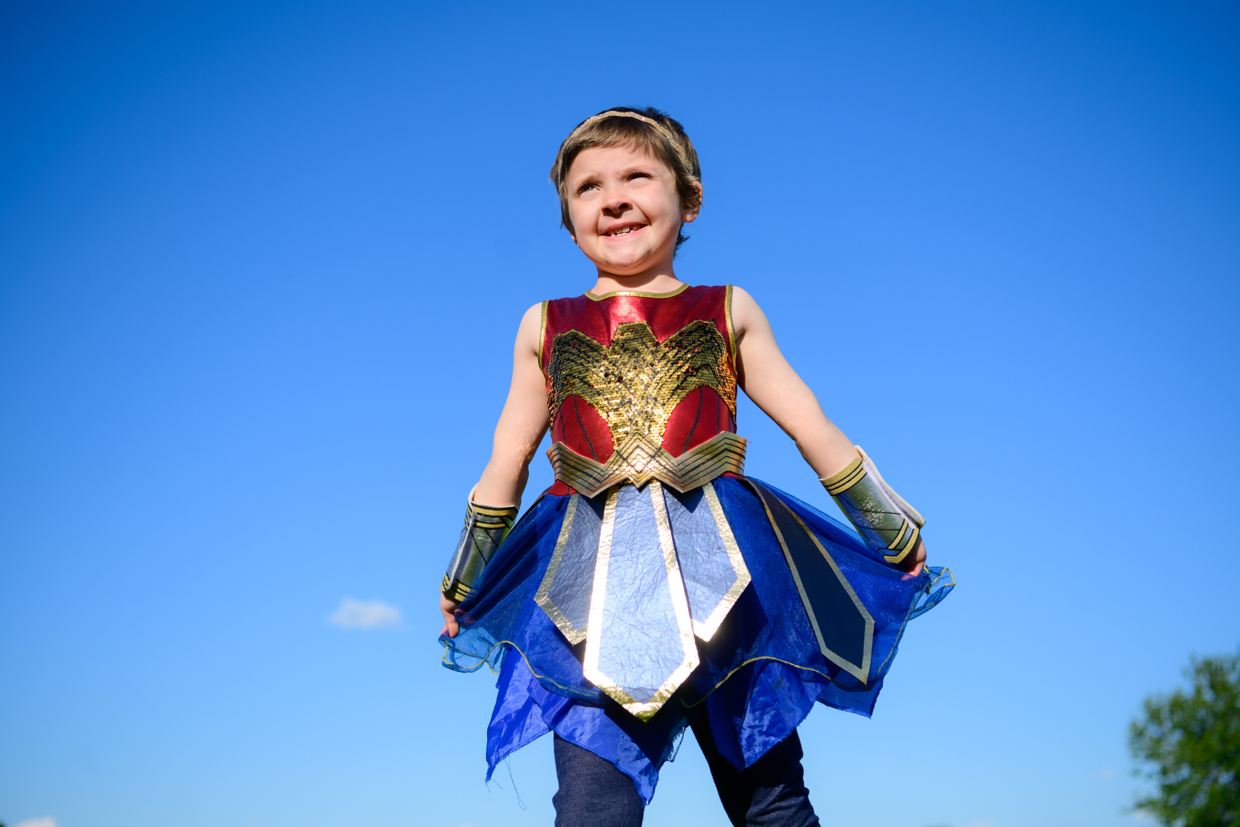 Leorah, a young white girl with short light brown hair, smiles as she stands in a field while wearing a Wonder Woman costume.