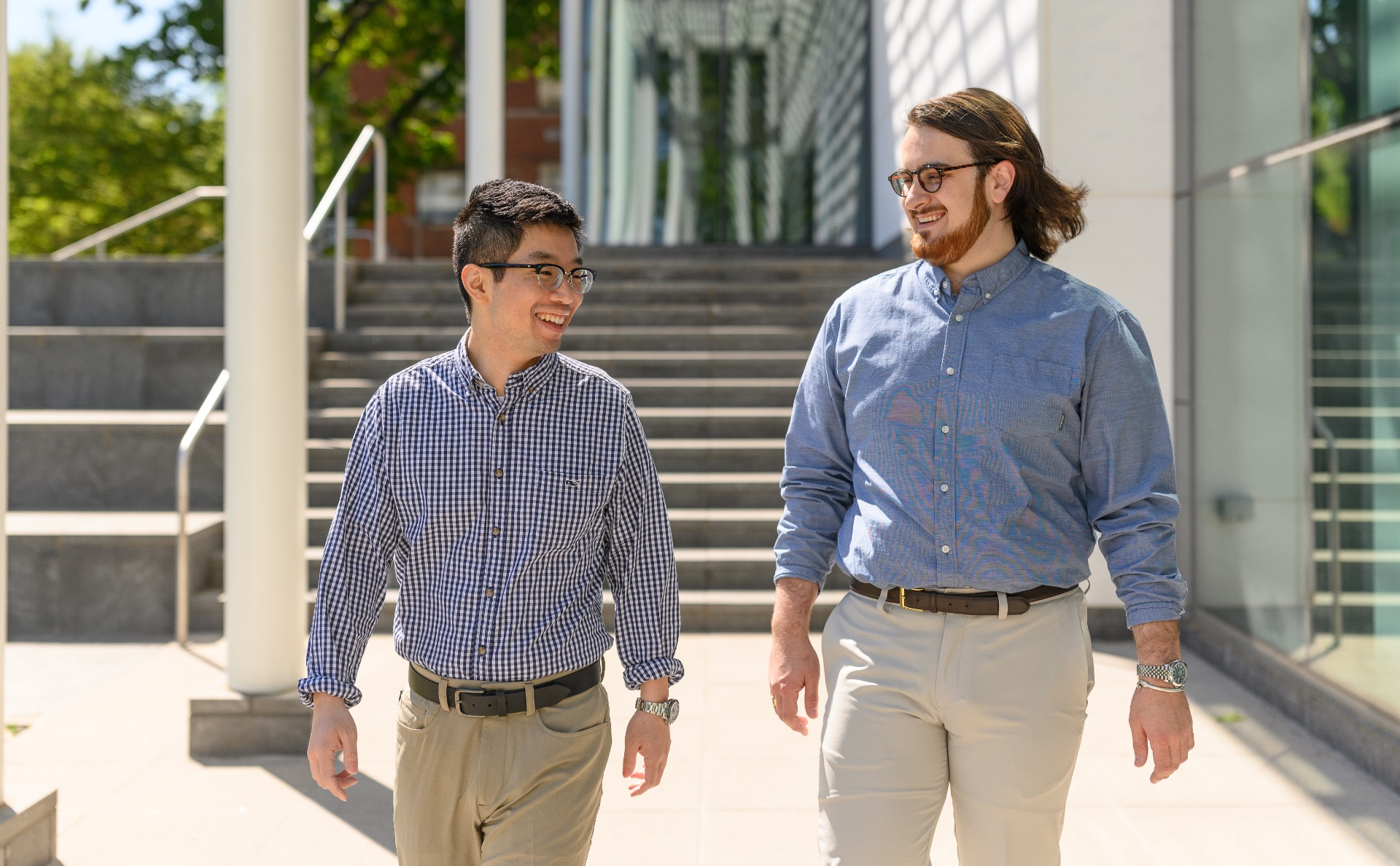 Ronnie and his roommate Zack, a young white man with long brunette hair, smile as they walk together outside. Zack is wearing a silver watch, round dark-framed glasses, and a white button-up shirt that is tucked into his khakis.
