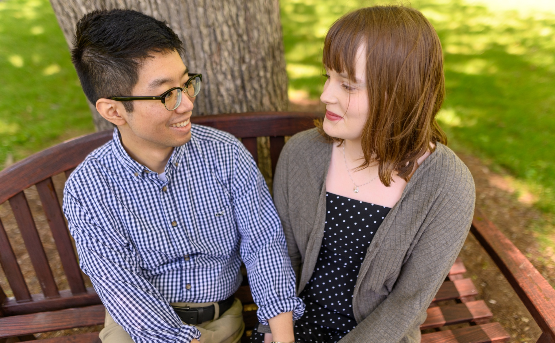 Ronnie and his girlfriend sit on a bench outside and smile at each other as they hold hands. She is a young white woman with light-brown hair in a mid-length cut, and she is wearing a grey sweater over a blue and white polka dot dress.