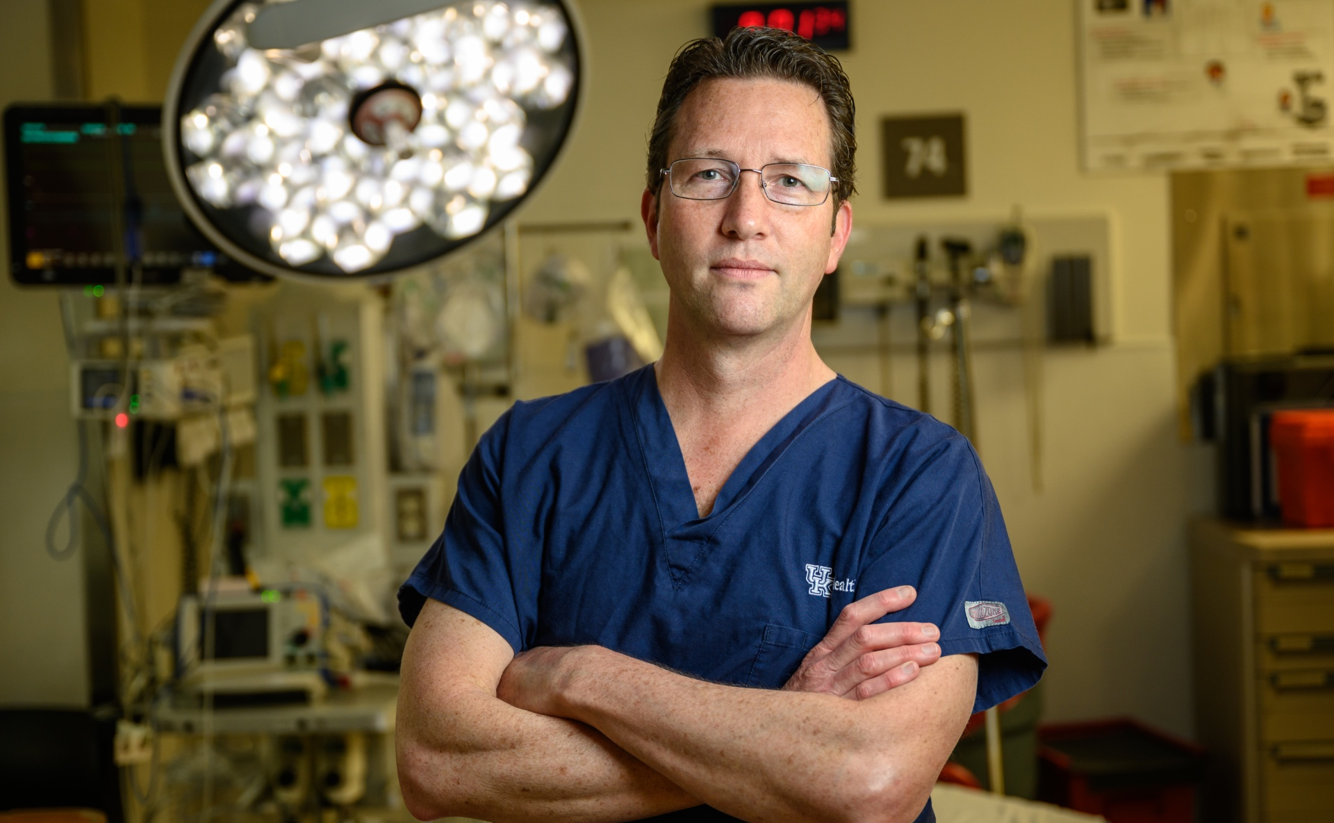Dr. Andrew Bernard, a white adult man with brown hair, stands confidently in an empty operating room with his arms crossed. He is wearing a blue set of scrubs, and a pair of glasses.