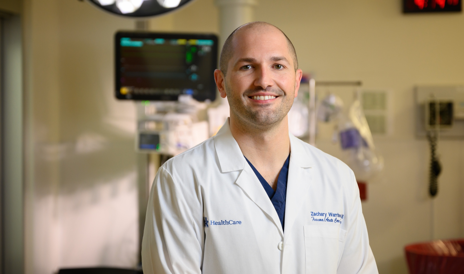 Dr. Zach Warriner, a white adult man with a shaved head, smiles while standing in front of medical equipment. He is wearing a white lab coat with a set of blue scrubs underneath.