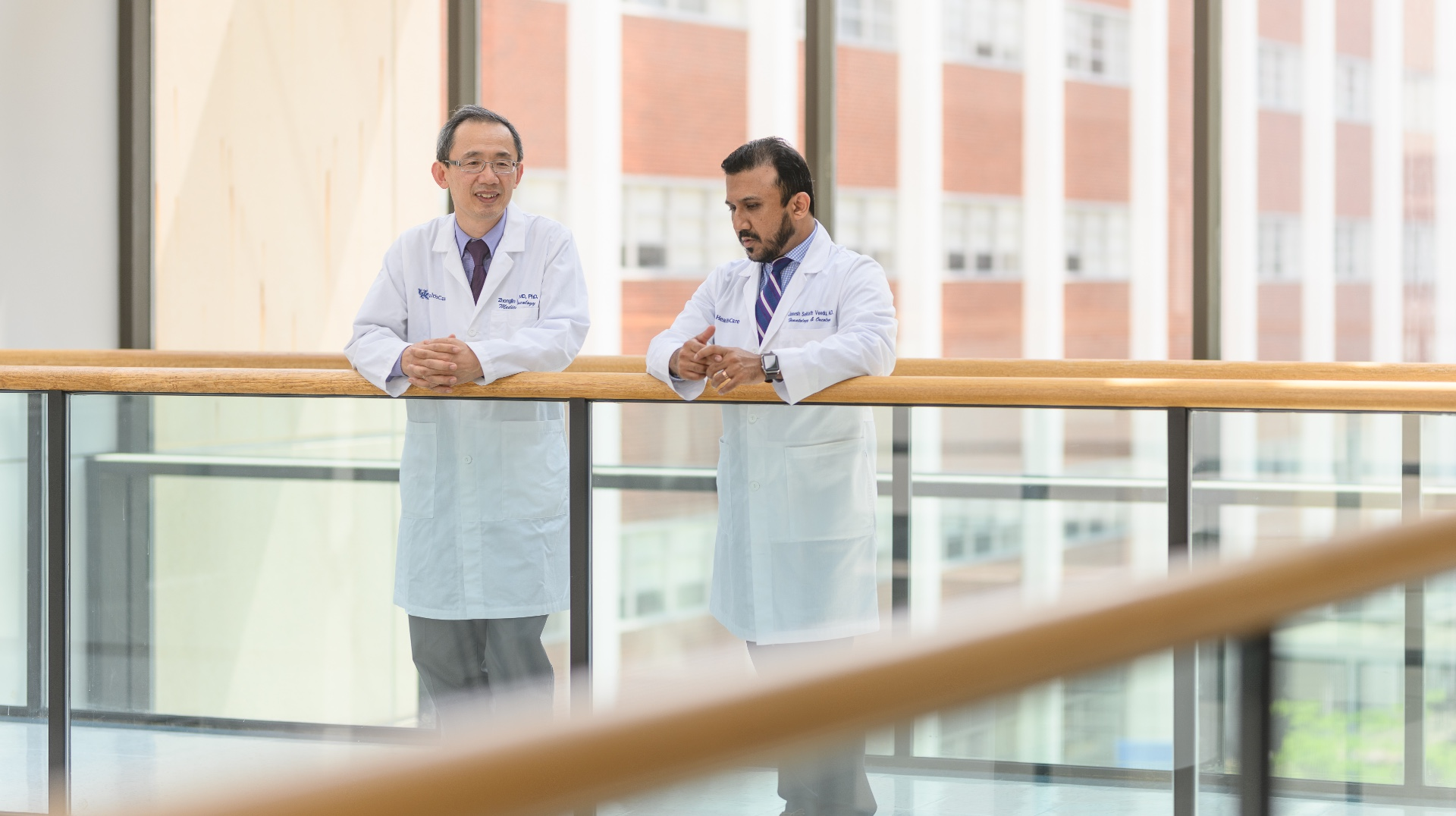 Dr. Zhonglin Hao, an older East Asian man with short greying hair, and Dr. Janeesh Sekkath Veedu, an older South Asian man with black hair, talk as they stand on a walkway in front of large glass windows. They are both wearing white lab coats with blue button-up shirts underneath. Dr. Hao is wearing glasses and a maroon tie, while Dr. Veedu is wearing a blue and white striped tie.