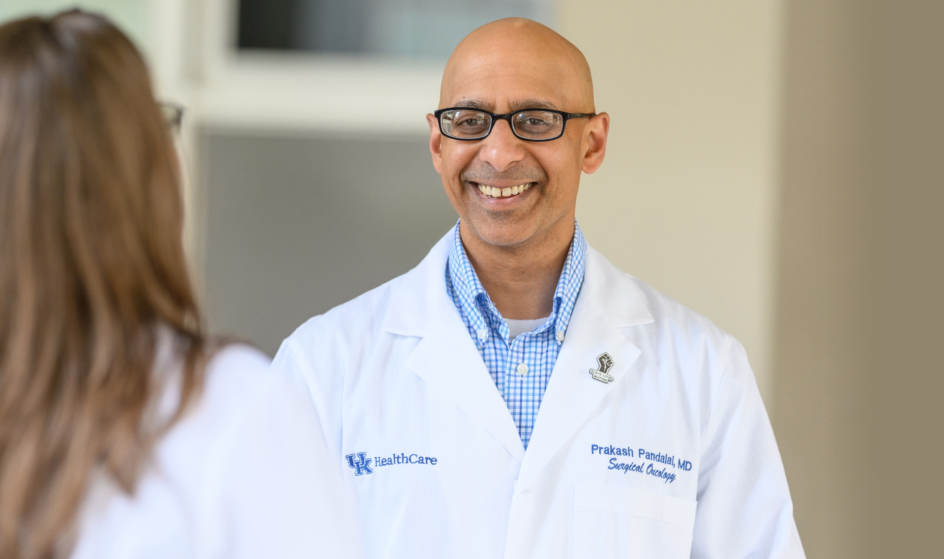 Dr. Prakash Pandalai, an older South Asian man with a bald head, smiles as he talks with a female colleague who has her back turned to the camera.