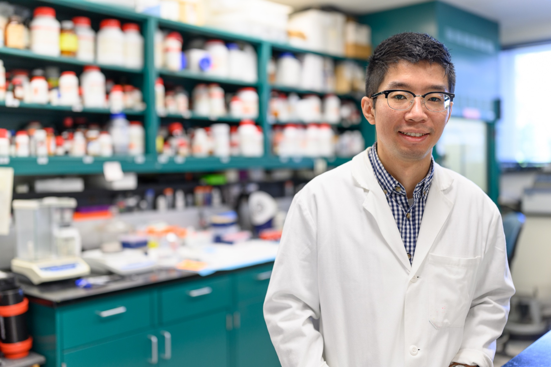 """Yueming """"Ronnie"""" Wu, a young East Asian man with short black hair, smiles for the camera as he stands in a laboratory. He is wearing a white lab coat over a blue gingham button-up shirt, and a pair of black-rimmed glasses."""