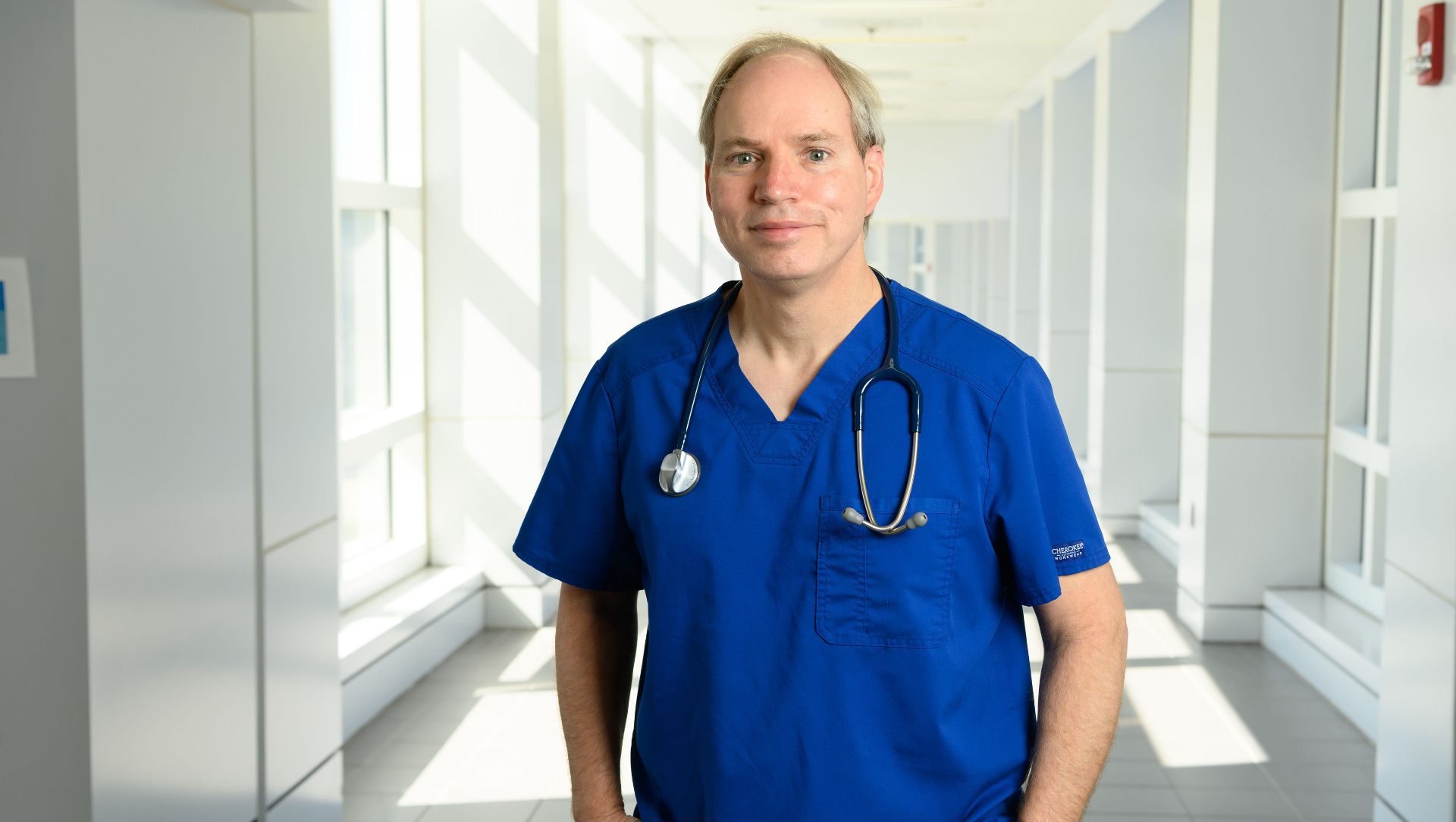 Dr. Michael Anstead, a middle-aged white man with grey hair, stands in the hallway of UK HealthCare wearing blue scrubs with a stethoscope around his neck.