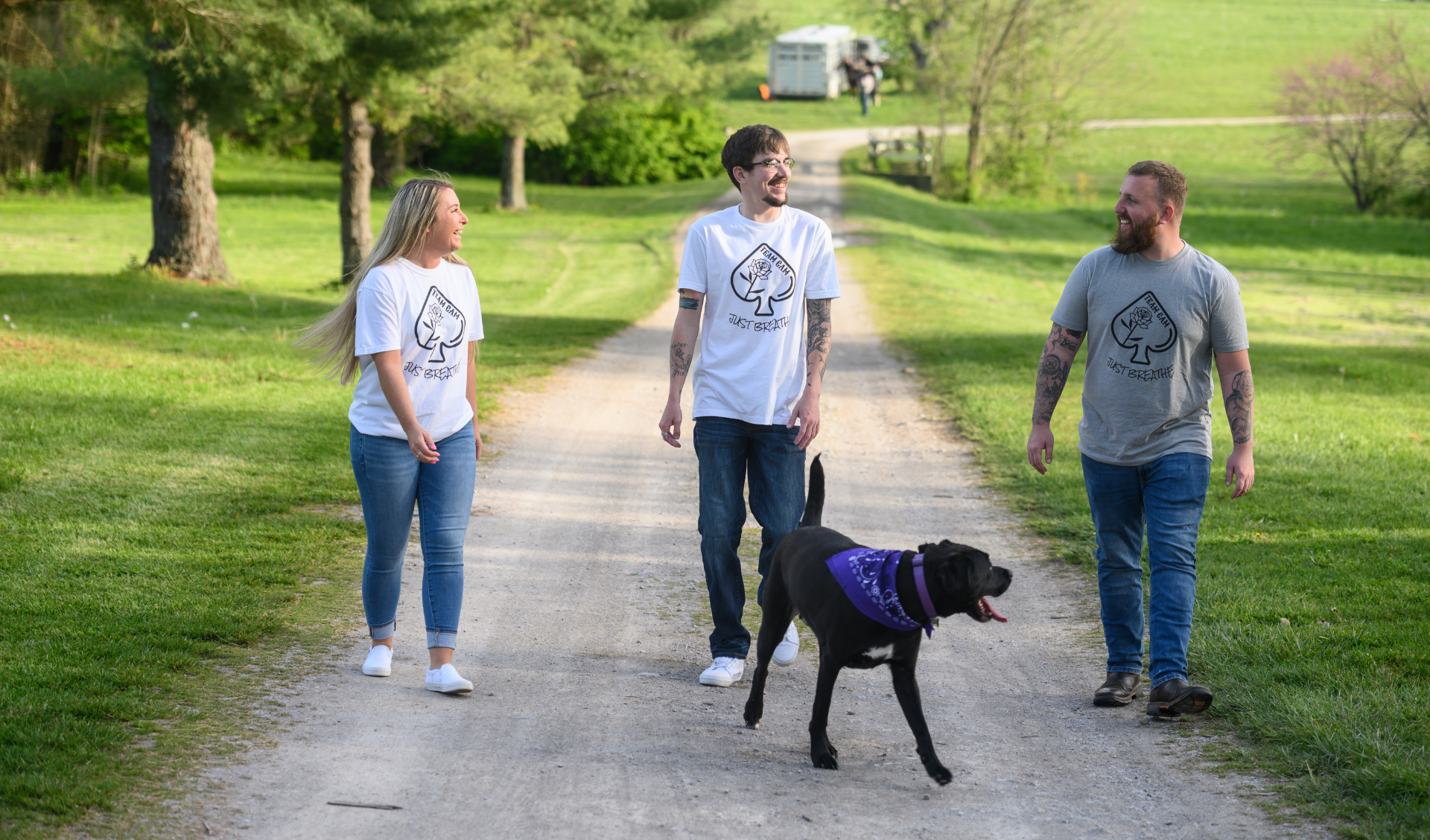 Cameron stands in between his friend Charlie, a white adult male with brown hair, and his fiance, Michelle, a white adult female with blonde hair. They are all wearing short sleeved specially designed 'Team Cam' shirts with a pair of jeans, while the dog walks ahead of them.