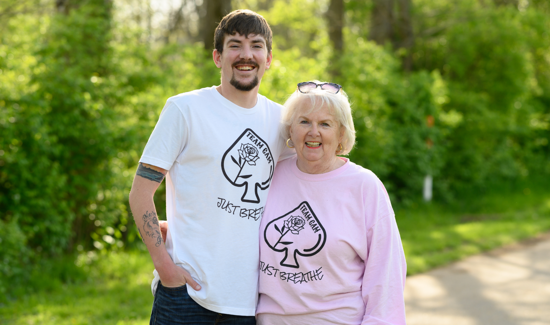 Cameron and his grandmother, an older white woman with white hair, stand and smile side by side. She is wearing a pink long sleeved 'Team Cam' shirt with her spectacles on her head.