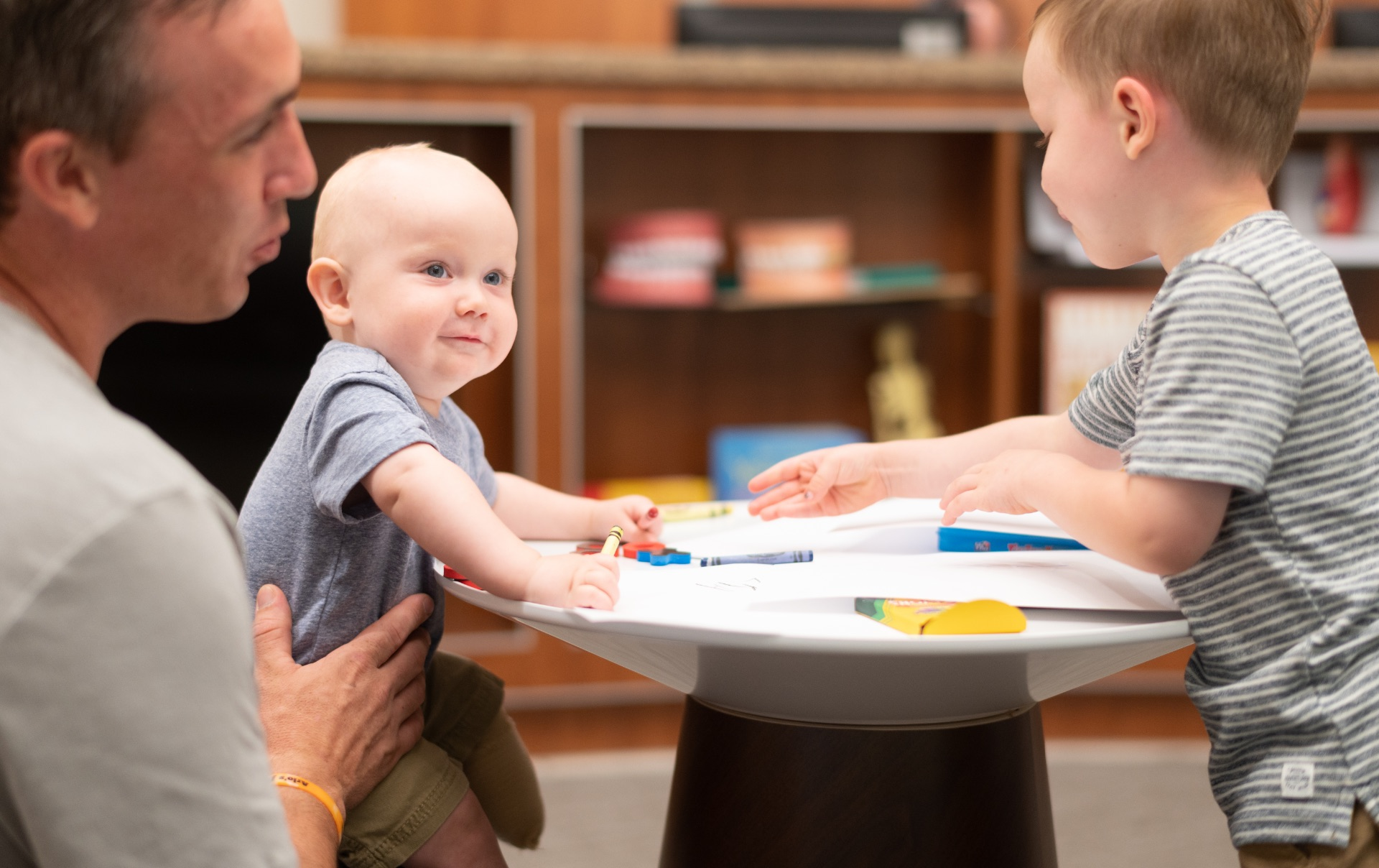 Tyler Yost holds his son Arlo while he's coloring alongside his older brother Ezra, who is a brunette white toddler that is wearing a grey and white striped shirt.