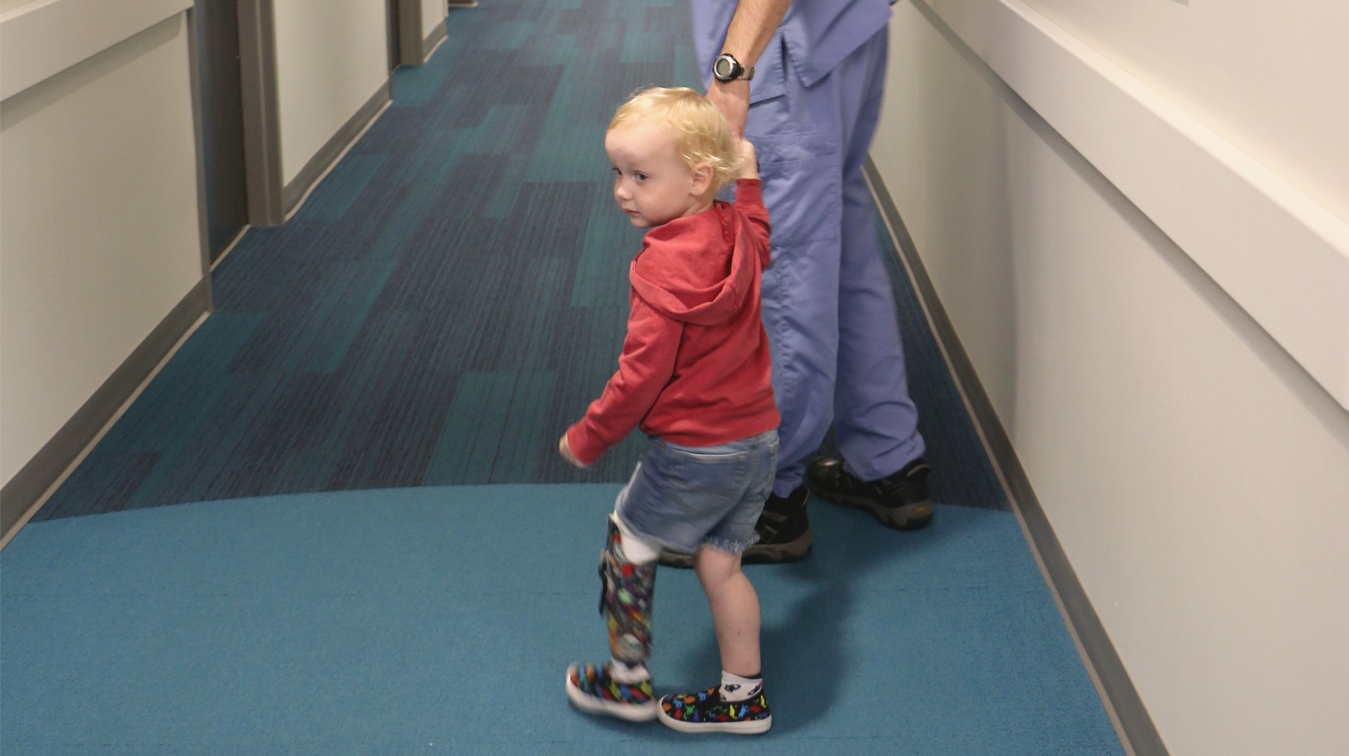 A doctor, who is out of frame, holds Arlo's hand as they walk together down a hallway.