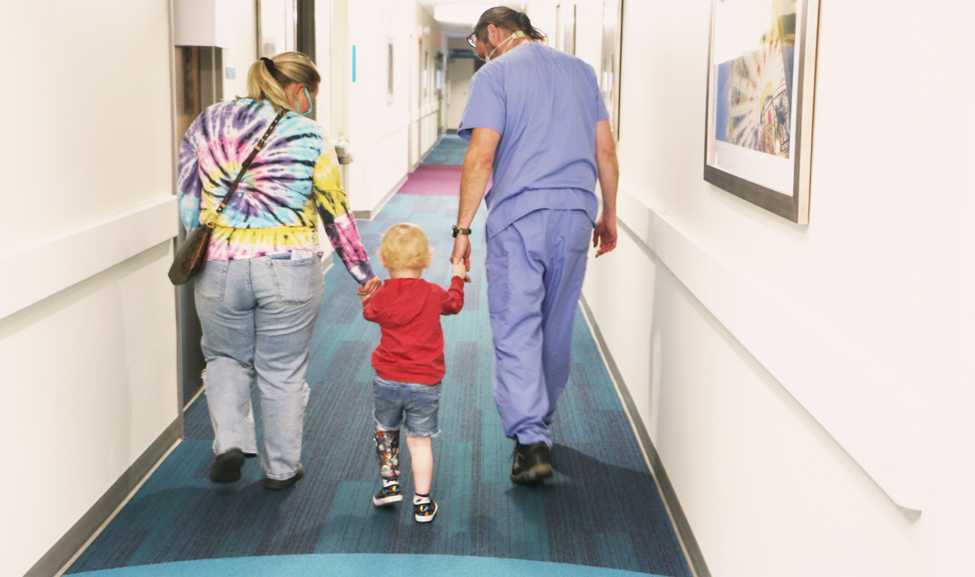 Arlo Yost is walking between his mother and Dr. Talwalkar, holding their hands as they make their way down the hallway.