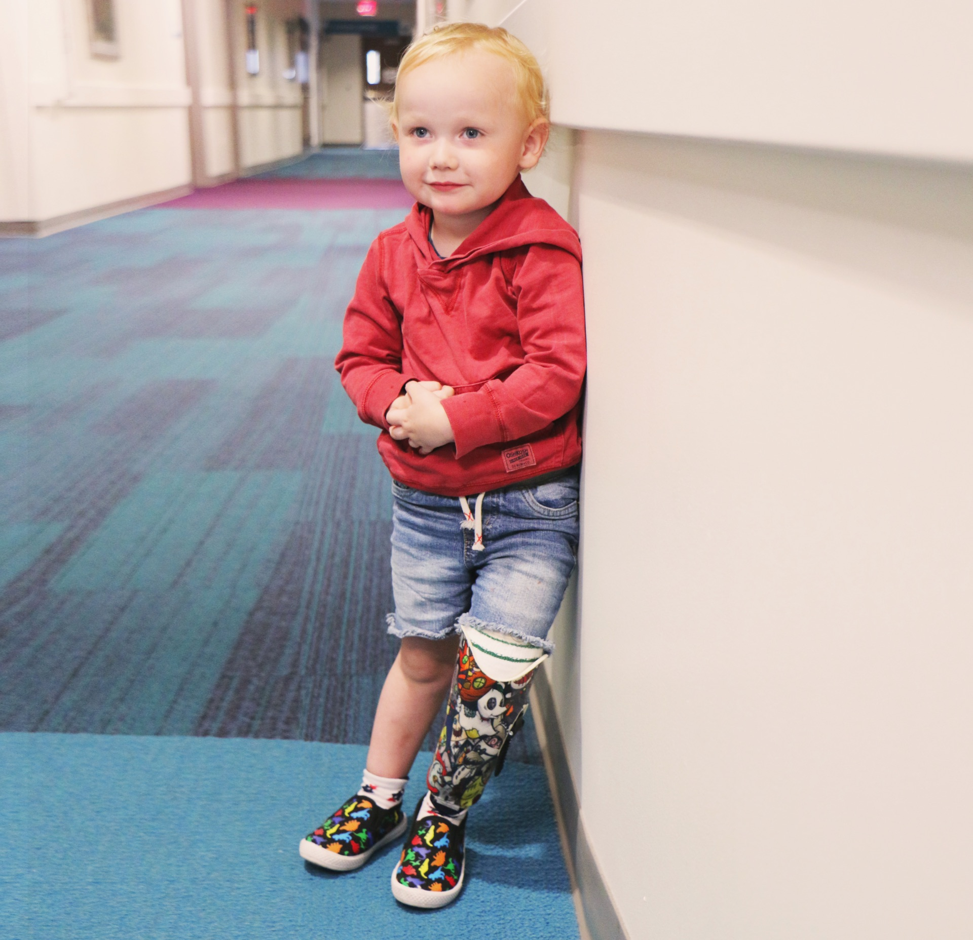 Arlo Yost leans against the wall of a hallway and smiles for the camera, with his prosthetic proudly visible.