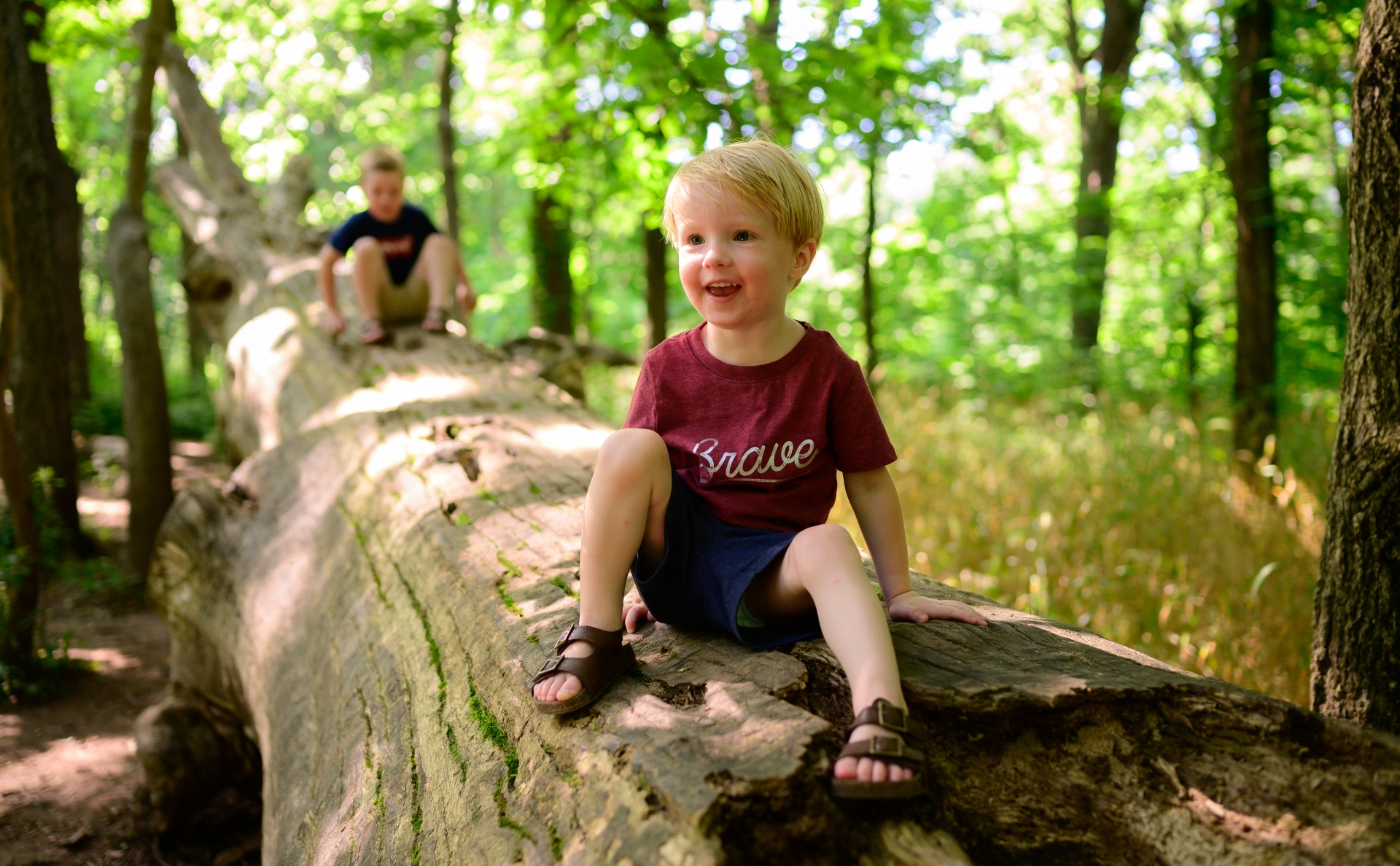Jeremiah, now a toddler, sits and smiles on a log out in the woods. Another child can be seen playing on the same log behind Jeremiah.