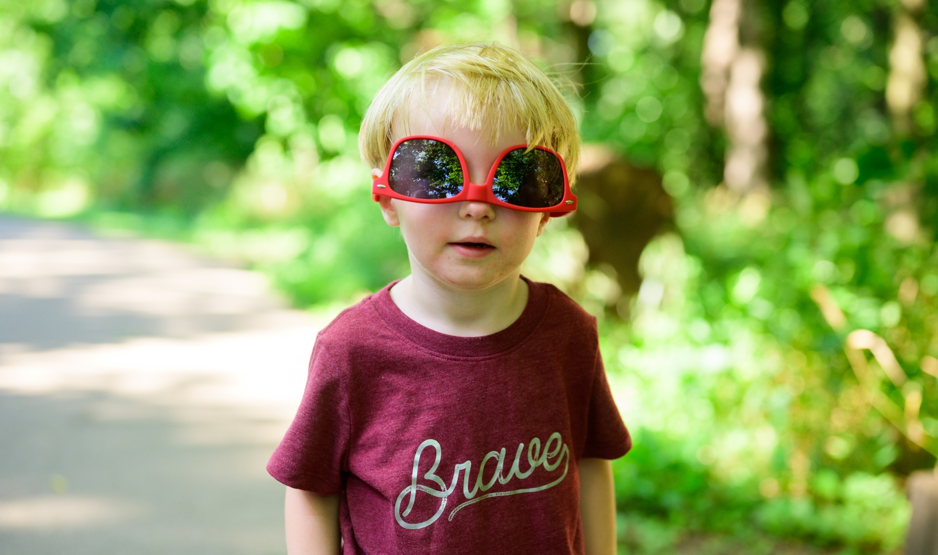 Jeremiah poses for the camera while wearing a pair of oversized sunglasses that are upside down on his face.