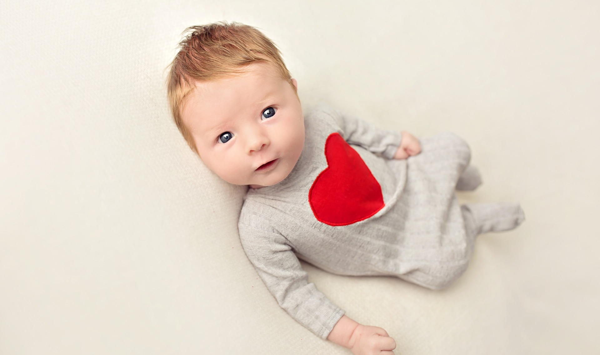A close-up of Jeremiah as an infant. He's looking up at the camera, while wearing a onesie that has a large red heart sewn onto it.