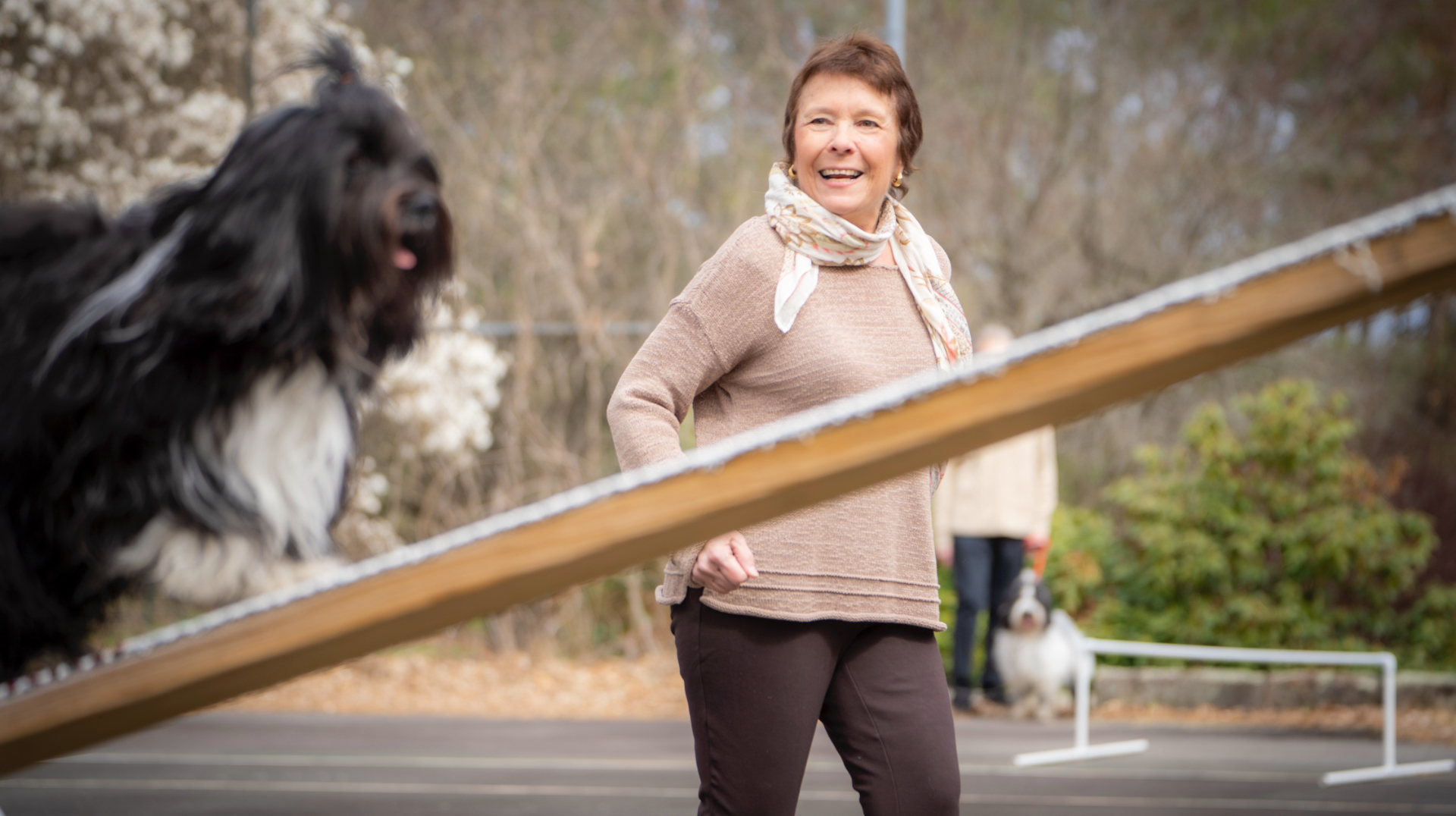 Dr. Irwin looks on proudly as she trains her dog Lucy in agility, keeping up with Lucy as she runs.