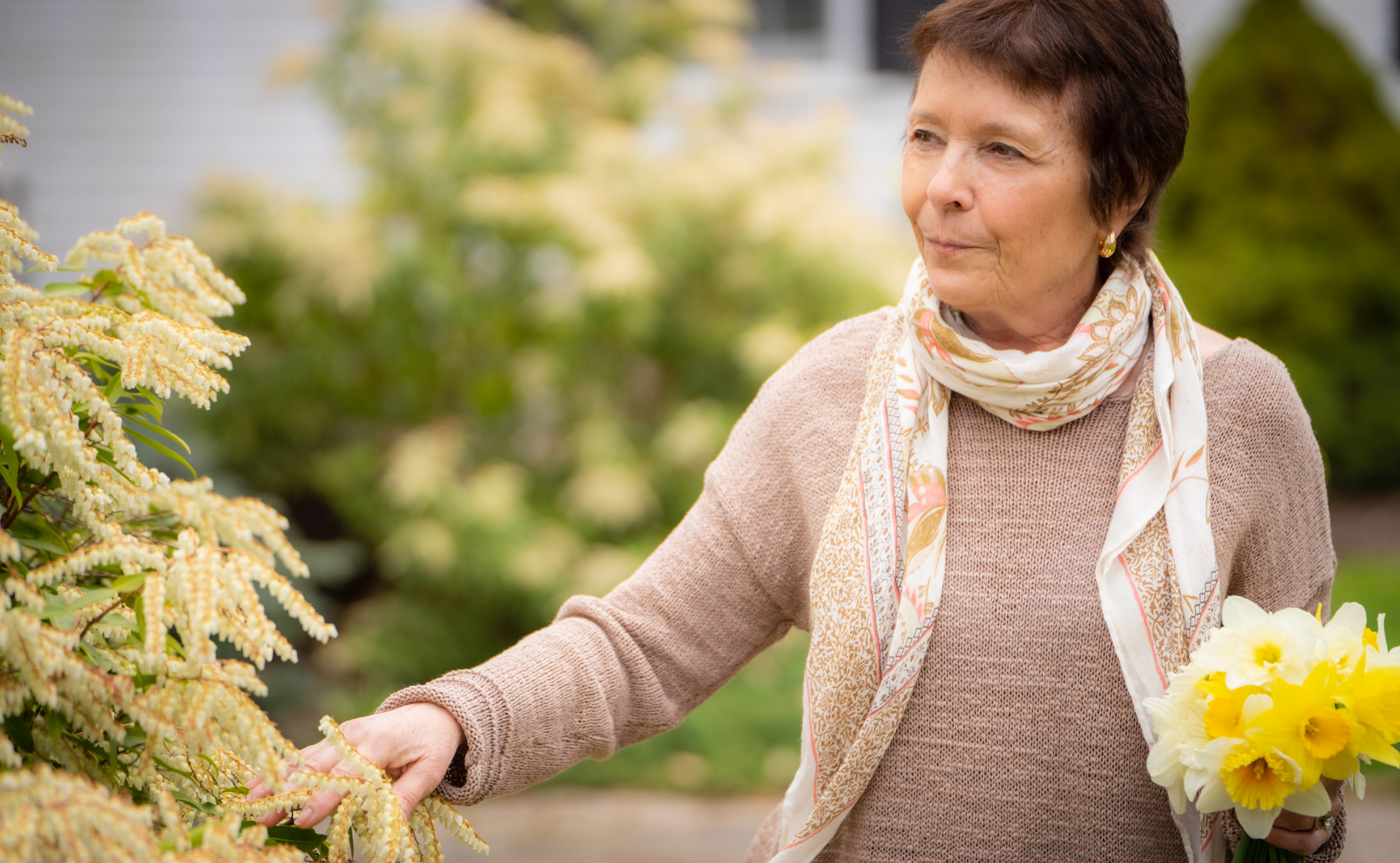 A candid shot of Dr. Irwin standing in her garden serenely admiring a plant, as she reached out to touch its white flowers.