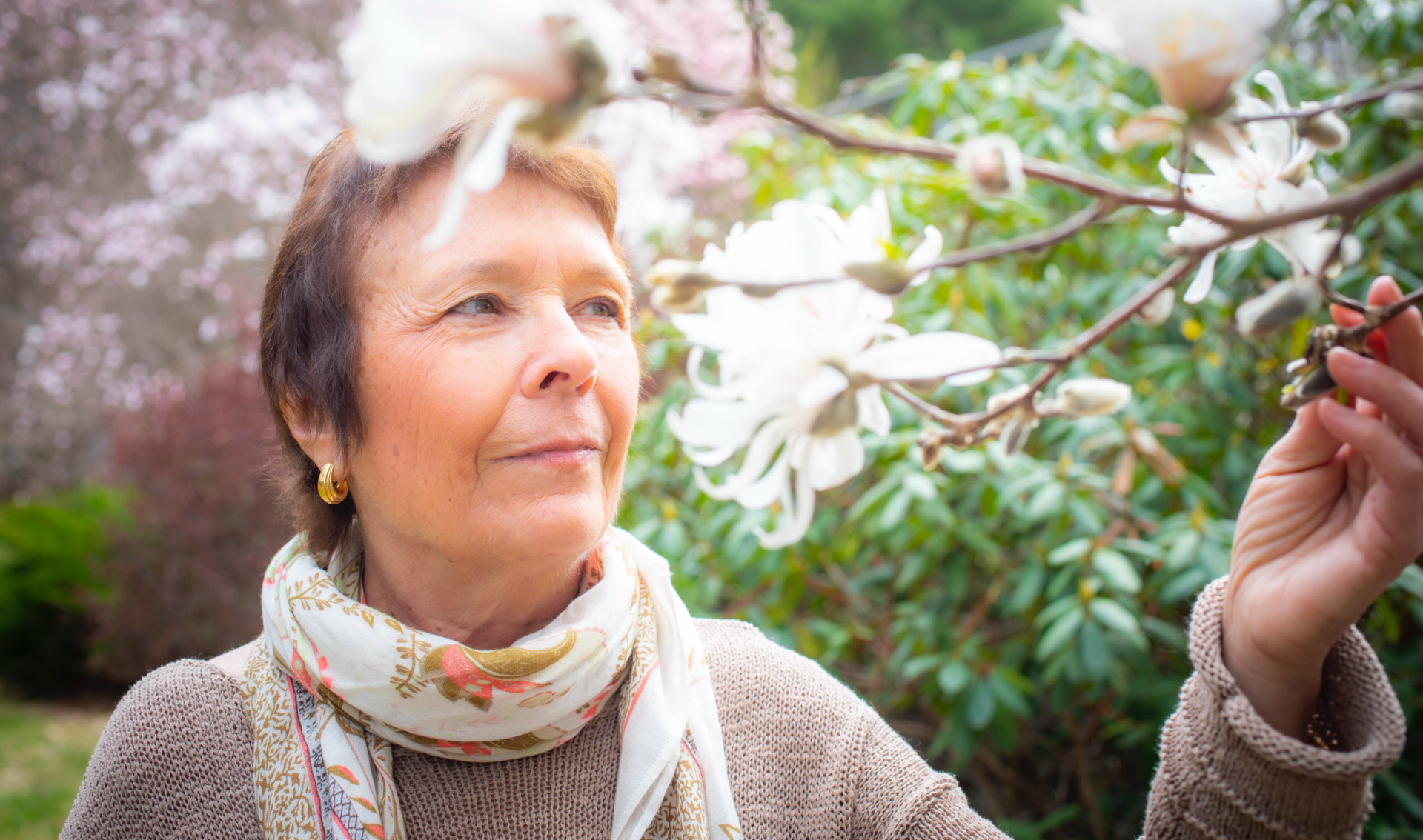 A close-up of Dr. Irwin standing in her garden thoughtfully appreciating a flowering tree, gently grasping one of its branches in her hand.