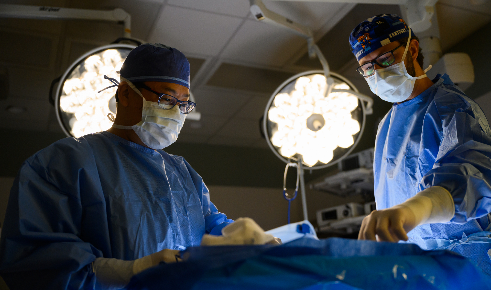 Dr. Kim (left) and Dr. Bell (right), a white with glasses and a brown beard, both in full surgical gear looked focused and determined as they stood over the operating table, while lights shine down on them.
