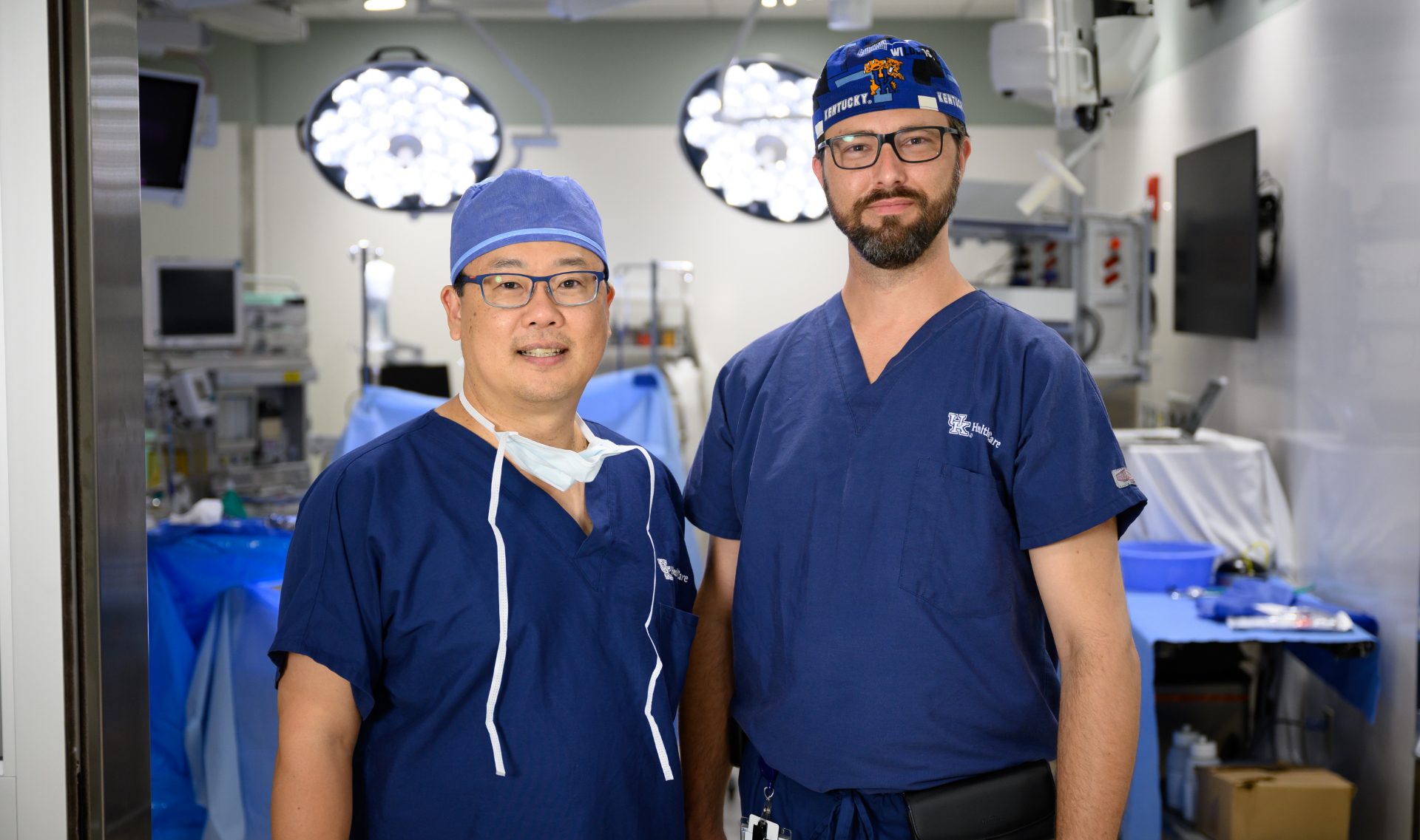 Dr. Kim (left) and Dr. Bell (right) confidently smiling for the camera in their scrubs, as they stand side by side outside the operating room.