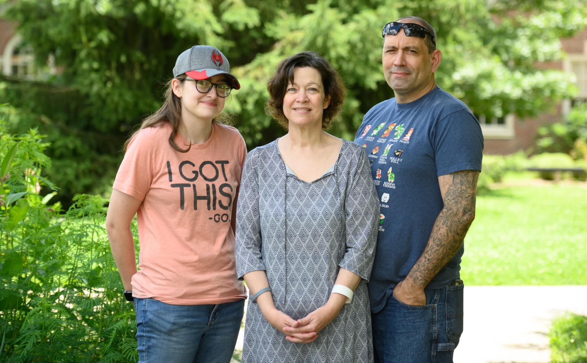 Kathy stands between her daughter, Caitlyn, and her husband, Robert, an older white man with a salt-and-pepper buzzcut and tattoos down his arm, as they all smile for the camera. He is wearing a Super Mario t-shirt, blue jeans, and a pair of black sunglasses on his head.