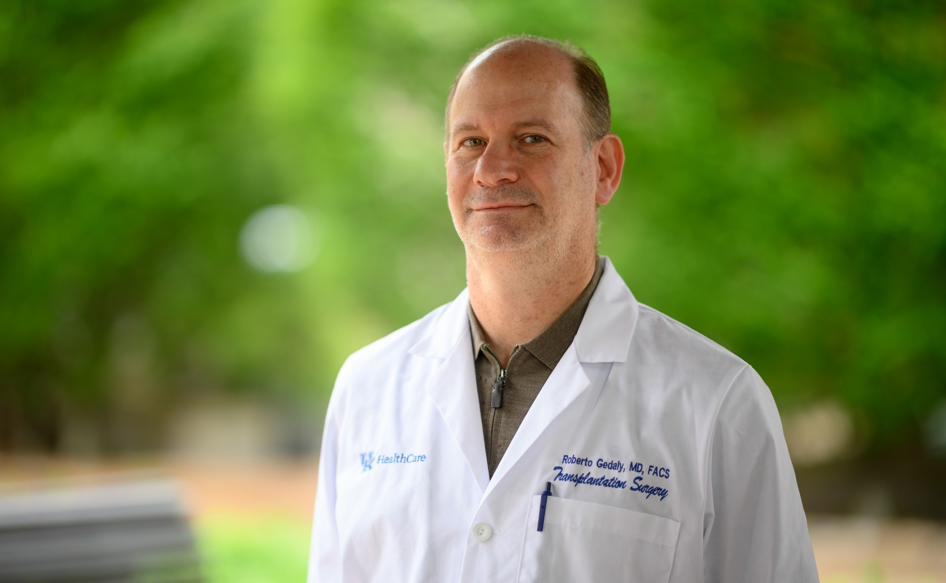 Dr. Roberto Gedaly, an older white man with greying brunette hair, smiles as he looks right at the camera. He is wearing a white lab coat over a brown zip-up shirt.