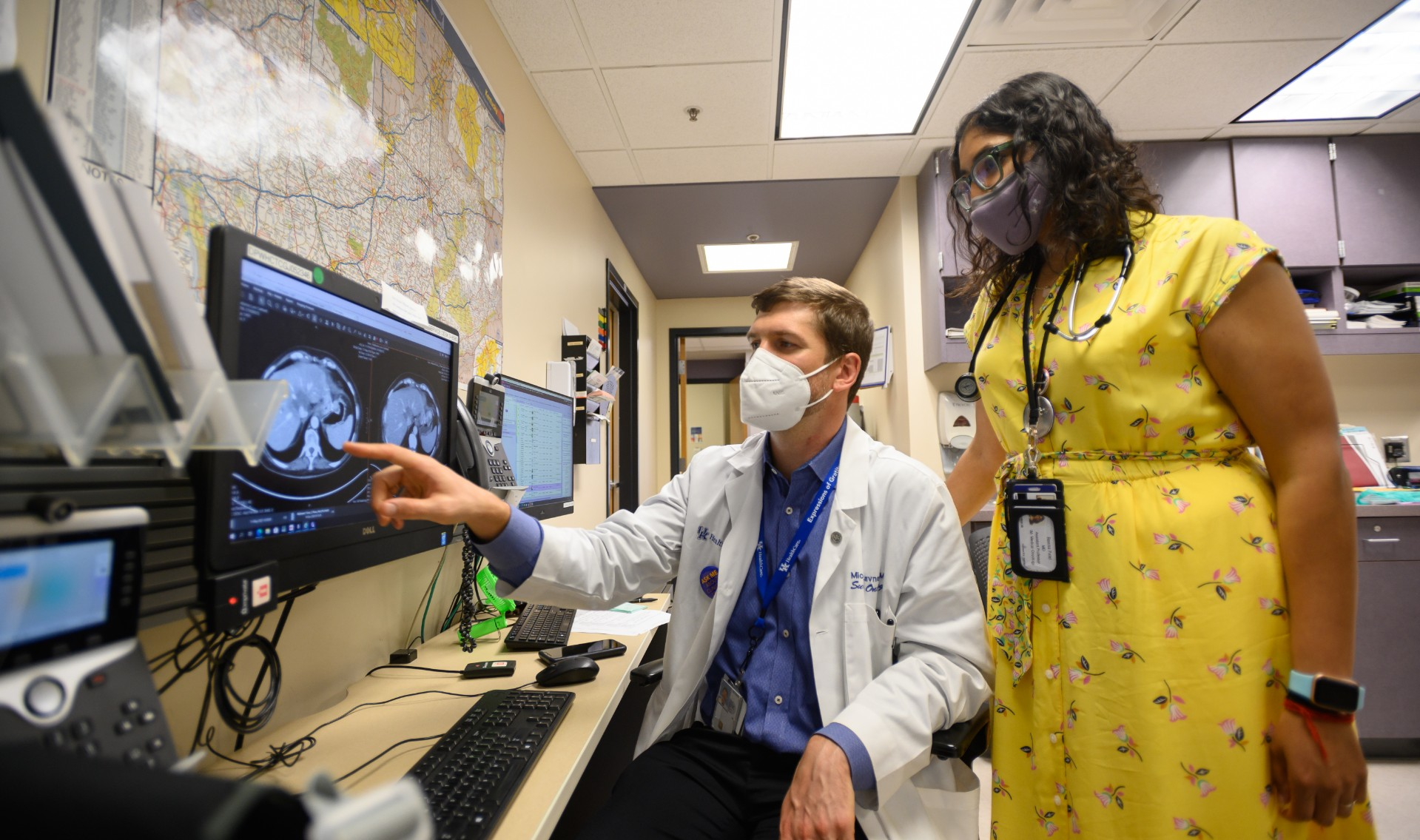 Dr. Michael Cavnar, an adult white man with brunette hair and white hairs peppered in his beard, analyzes Kathy's scans alongside Dr. Reema Patel, a young South Asian woman with curly black hair. Dr. Cavnar is wearing a white lab coat over a blue button-up shirt, and a face mask. Dr. Patel is wearing a yellow floral dress, her credentials and stethoscope around her neck, a pair of green-framed glasses, and a face mask.