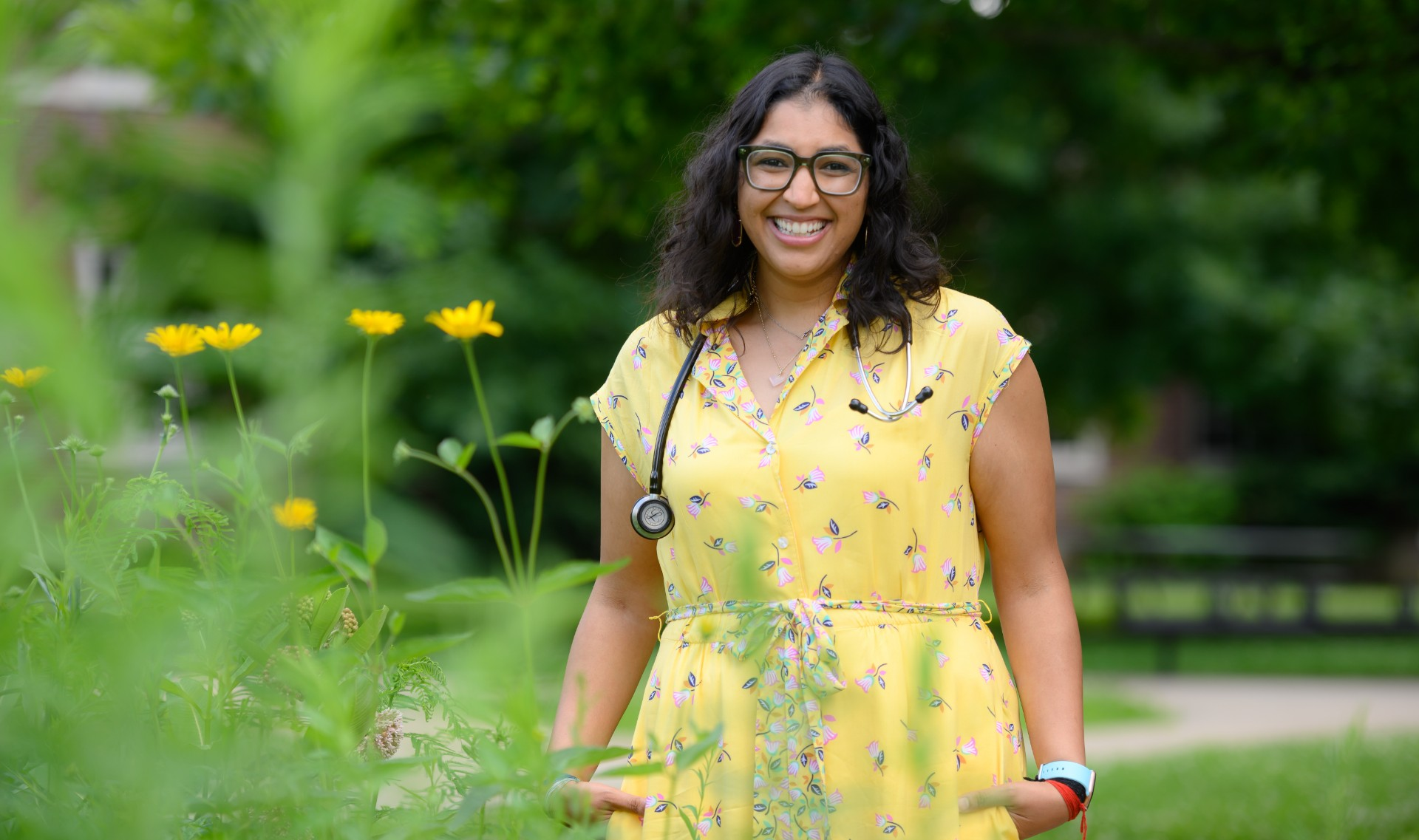 Dr. Patel stands next to some yellow flowers as she smiles directly at the camera.